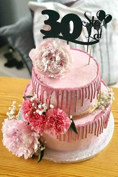 Piętrowy różowy tort urodzinowy z kwiatami